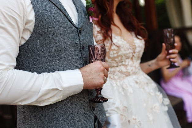 Mains de mariées avec des verres décorés. deux verres décorés avec un champagne dans les mains de la mariée et du marié. 2 verres à vin décorés. lieu de célébration de mariage. fête de mariage