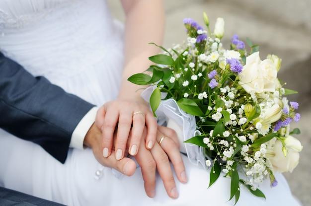 Les mains des mariés avec des alliances