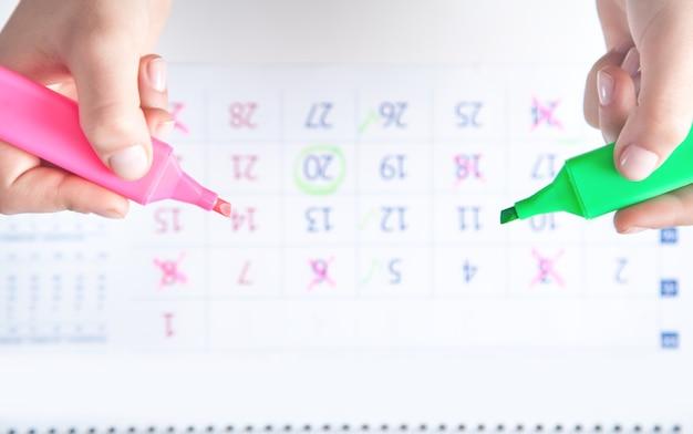 Les mains marquent le calendrier avec un marqueur.