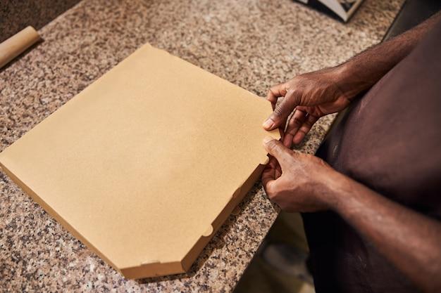 Mains masculines afro-américaines emballant la pizza fraîchement cuite dans la boîte de livraison