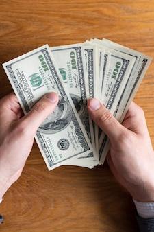 Mains masculines comptant des billets en dollars américains ou payant en espèces sur fond d'argent