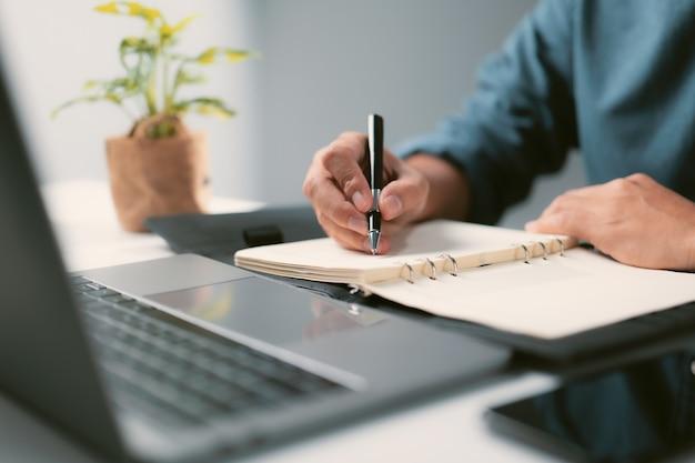 Mains masculines avec un crayon écrivant la liste à faire dans le bloc-notes avec un ordinateur portable