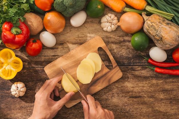 Mains masculines faisant cuire la salade de légumes dans la cuisine