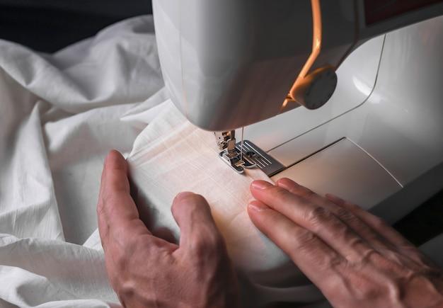 Mains masculines faisant du point sur le textile sur la couture manuelle de la machine à coudre