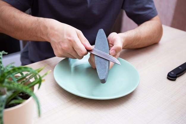 Des mains masculines fortes en gros plan affûtent un couteau en métal de cuisine avec une meule. affûtage de couteaux ménagers à domicile.