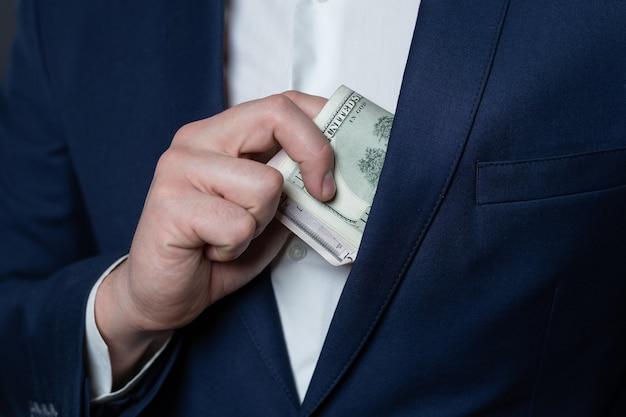 Les Mains Masculines Mettent Des Dollars Dans Sa Veste De Poche Photo Premium