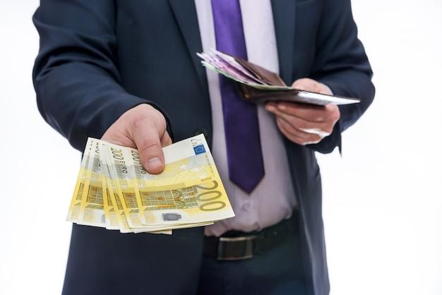 Mains masculines offrant des billets en euros en ventilateur
