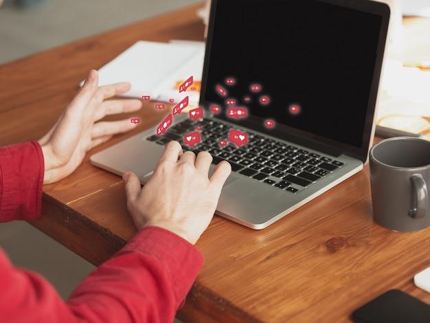 Mains masculines tapant du texte, un message et partageant avec les médias sociaux, à l'aide d'un ordinateur portable. obtenez des commentaires, des likes. icônes d'interface utilisateur modernes, communication, appareils. concept de technologies modernes, de mise en réseau, de gadgets. concevoir.