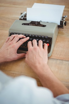 Mains masculines en tapant sur une vieille machine à écrire sur une table en bois