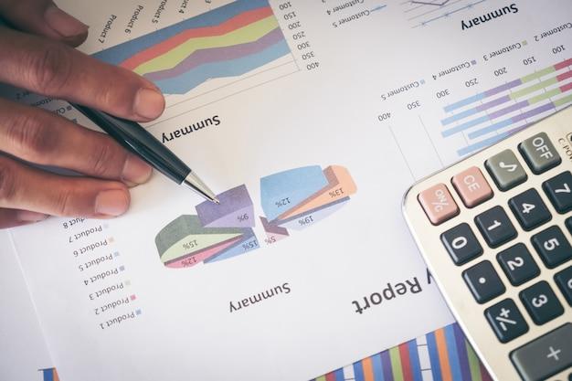 Les mains masculines tenant un ballpoint et en analysant le diagramme financier