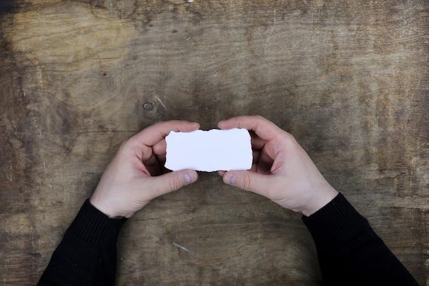 Mains masculines tenant une feuille de papier vierge blanche sur le fond de la table de texture en bois