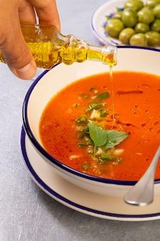 Des mains masculines versent de l'huile d'olive d'un récipient en verre dans un gaspacho espagnol traditionnel à base de tomate, de poivre et d'ail avec l'ajout de sauce tabasco