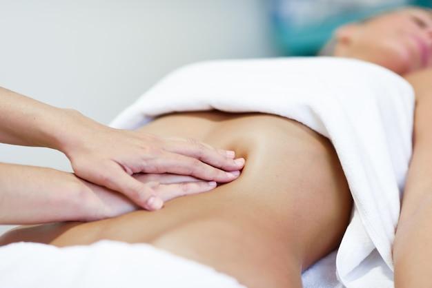 Les mains massent l'abdomen féminin. le thérapeute exerce une pression sur le ventre.
