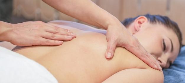 Mains de massothérapeute faisant massage sur le dos de la jeune fille