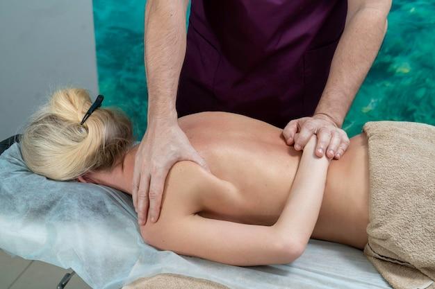 Mains d'un massothérapeute massant une femme