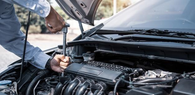 Mains de mécanicien automobile à l'aide d'une clé pour réparer un moteur de voiture.