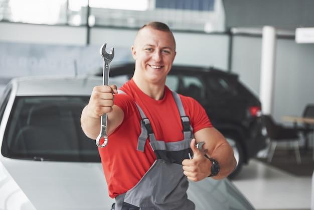 Mains de mécanicien automobile avec clé dans le garage.