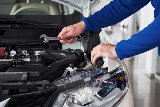 Mains de mécanicien automobile avec clé dans le garage