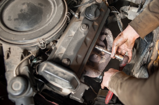 Mains de mécanicien réparateur travaillant sur le moteur à l'aide d'un outil