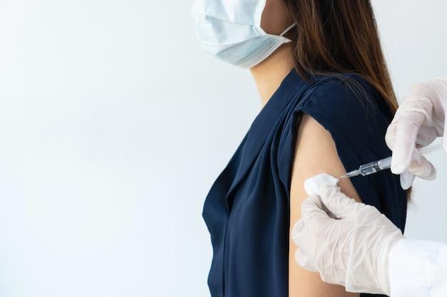 Mains d'un médecin ou d'une infirmière tenant une seringue faisant une dose d'injection de vaccination covid 19 dans l'épaule d'une patiente. concept d'essais cliniques du vaccin contre la grippe. gros plan, copiez l'espace