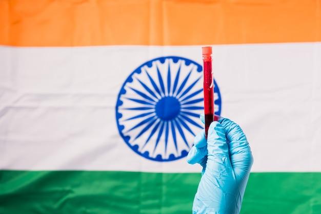 Mains d'un médecin portant des gants tenant le coronavirus du tube à essai sanguin