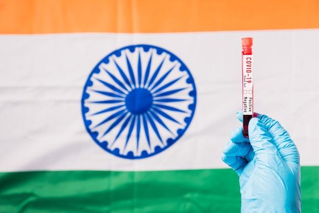 Mains d'un médecin portant des gants tenant le virus du coronavirus du tube à essai sanguin (covid-19) dans le laboratoire sur le drapeau inde