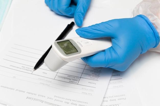 Les mains des médecins dans les gants tiennent un thermomètre sans contact pour mesurer la température avant d'être vacciné à covid19 le concept de vaccination santé médicale contre le virus covid19