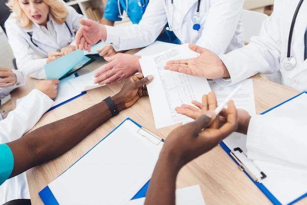 Mains de médecins de différentes races.
