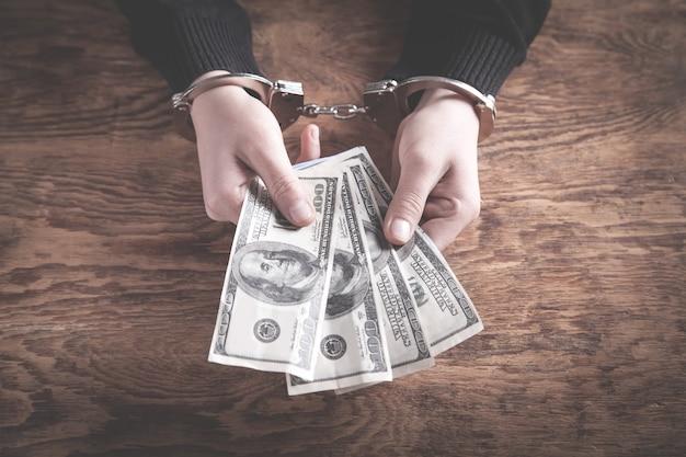 Mains menottes aux poignets tenant des billets en dollars. la corruption