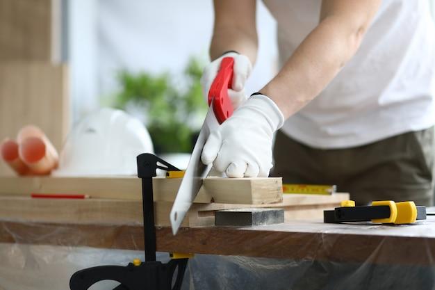 Mains de menuisier sciant du bois en bois