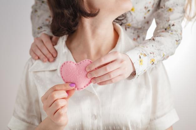 Les mains de la mère et la main d'un enfant tenant un coeur rouge ensemble