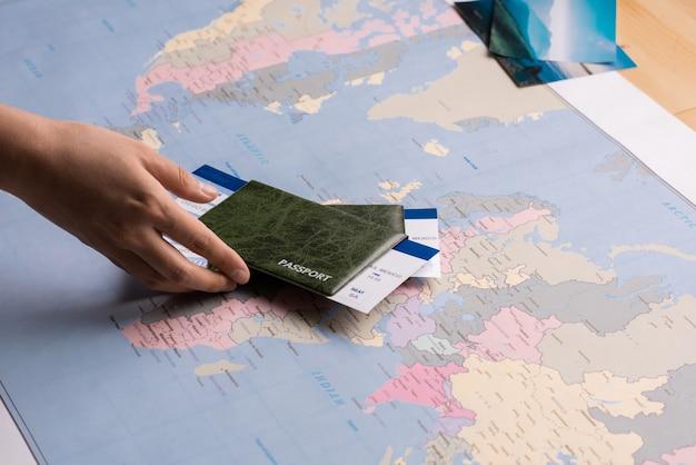 Mains mettant des passeports avec des billets sur la carte du monde lors de la préparation du voyage