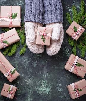 Mains en mitaines tenant une boîte de cadeau de noël