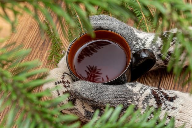 Mains en mitaines tenant une tasse de thé en gros plan sur le brun brossé