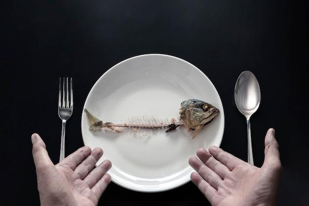Les mains montrent des arêtes de poisson à manger