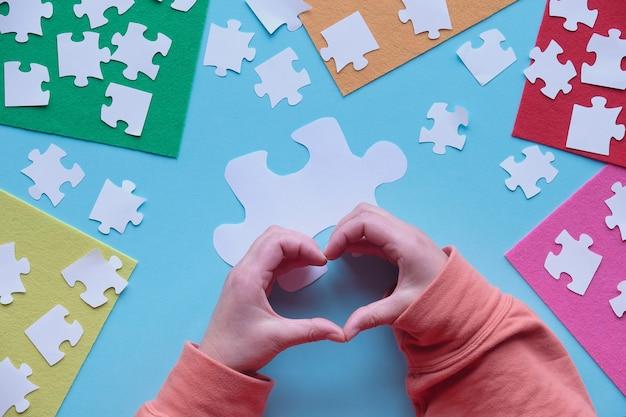 Les mains montrent le signe du cœur. éléments de puzzle et feuilles de feutre multicolores