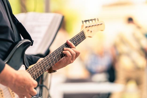 Mains d'un musicien jouant de la guitare électrique lors d'un concert en direct