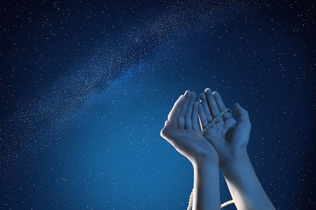 Mains musulmanes priant avec des perles de prière en plein air