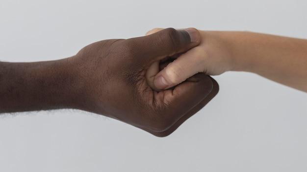 Mains noires et blanches tenant