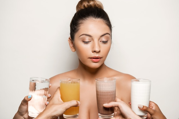 Mains offrant de l'eau, du jus, du café ou du lait à une belle femme