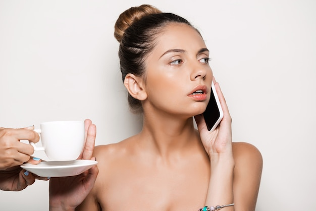 Mains offrant une tasse de café à une femme parlant au téléphone