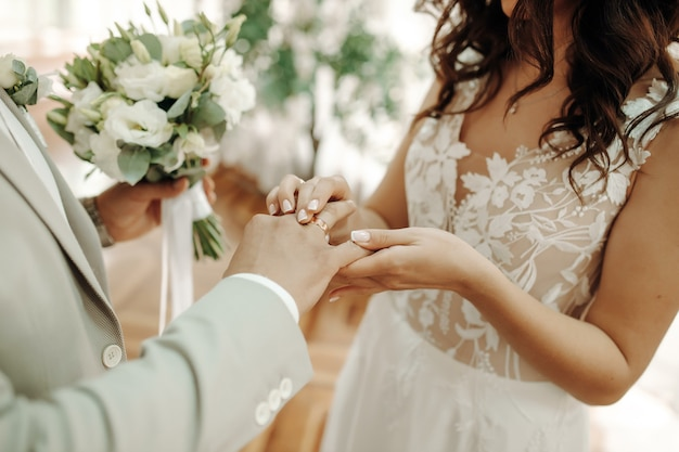 Mains omains de jeunes mariés avec des anneaux de mariage et un bouquet de mariage. les jeunes mariés avec des alliances et un bouquet de mariage.