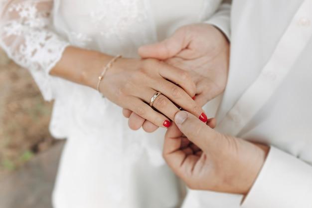 Mains omains de jeunes mariés avec des anneaux de mariage et un bouquet de mariage de jeunes mariés