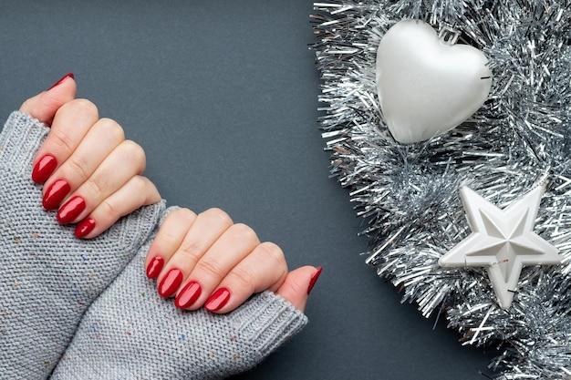 Mains avec des ongles scintillants rouges