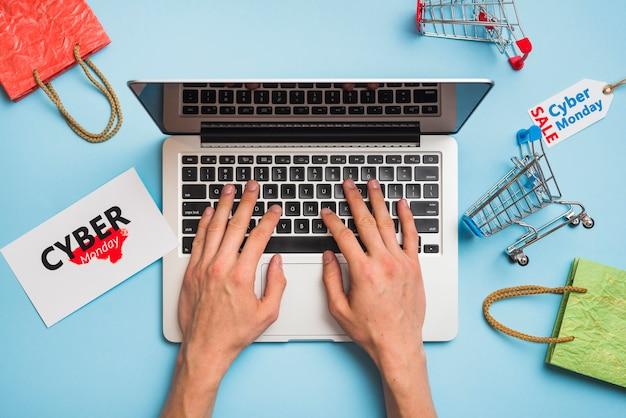 Mains sur un ordinateur portable près des balises portant le titre de cyber monday