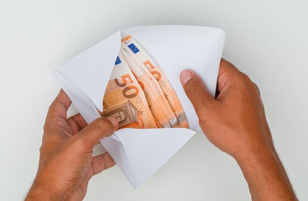 Mains ouvrant l'enveloppe pleine de billets de banque.
