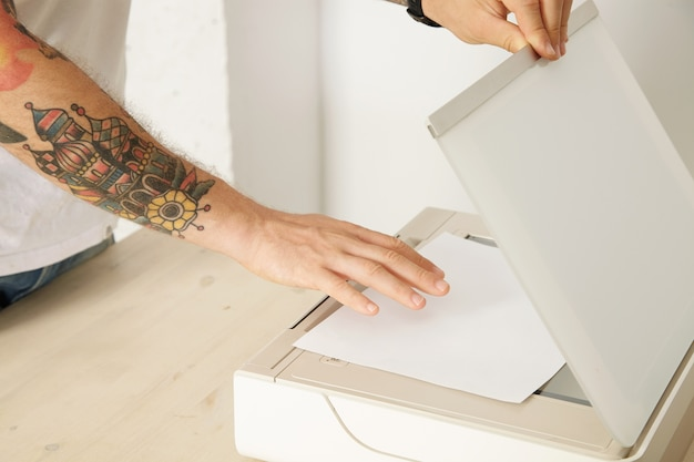 Mains ouvrent un plateau de scanner et mettre une feuille de papier pour numériser un document à l'intérieur d'un appareil électronique multifonctionnel, isolé sur une table en bois blanc,