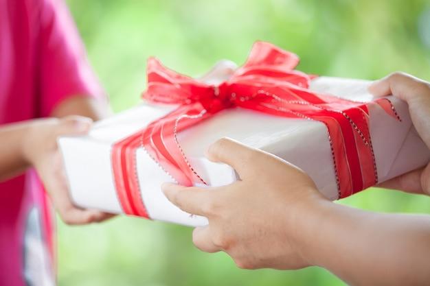 Mains de parent donnant le cadeau de noël à l'enfant fille sur fond de nature verdoyante. concept de noël.