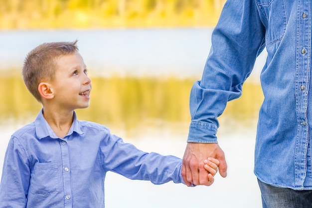 A mains de parent et enfant dans la nature dans le parc voyage