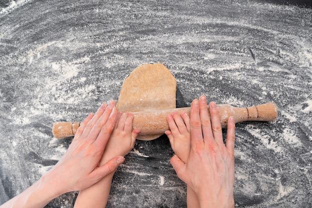 Les mains des parents et de l'enfant déroulent la pâte à biscuits maison.